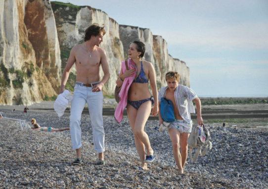 Tre ungdomar på stenig strand